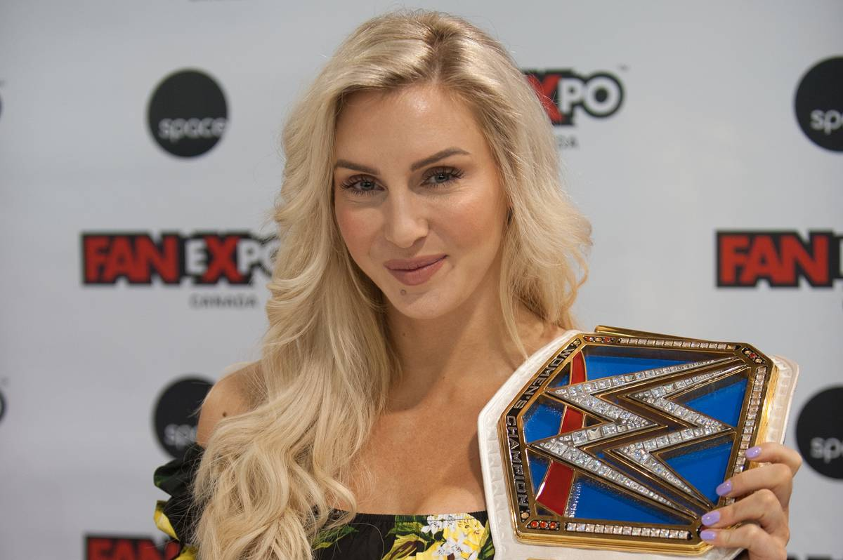 charlotte flair posing with her WWE championship belt
