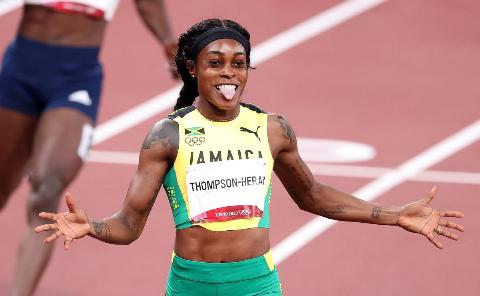 Elaine Thompson-Herah celebrates winning a gold medal during the Tokyo Olympics.